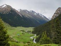 Valle de la montaña cubierto con árboles de pino, un río y las casas en t foto de archivo libre de regalías