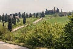Valle de Toscana con el solo camino del carril Imagen de archivo libre de regalías
