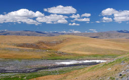 Valle del río de la montaña con nieve en la alta meseta Fotos de archivo libres de regalías