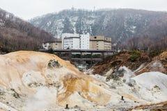 Valle dell'inferno di Noboribetsu Jigokudani con l'hotel e la montagna: La valle del vulcano ha ottenuto il suo nome dall'odore s immagine stock libera da diritti