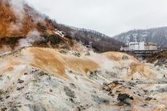 Valle dell'inferno di Noboribetsu Jigokudani con l'hotel e la montagna: La valle del vulcano ha ottenuto il suo nome dall'odore s fotografia stock libera da diritti