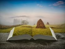Valle della montagna con i mucchi di fieno alle pagine del libro immagini stock