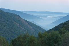 Valle della montagna nella nebbia, orizzontale. Immagine Stock