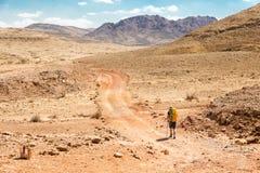 Valle di pietra d'escursione turistica Ramon Israel della traccia del deserto di viaggiatore con zaino e sacco a pelo Fotografia Stock