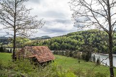 Valle e lago di Zaovine veduti dalla cima di una scogliera, con una casa del paesino di montagna nella priorità alta, circondata  Immagine Stock