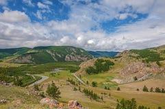 Valle, foresta, fiume, strada, cielo blu e nuvole della montagna Immagini Stock