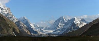 Valle glaciale delle alte montagne: i picchi coperti di ghiaccio eterno, moraine discende al fiume, nuvole si trovano fra le mont Fotografia Stock