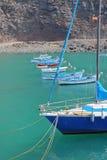 VALLE GRAN REY, LA GOMERA, SPANIEN - 19. MÄRZ 2017: Das Dorf von Vueltas mit Segelbooten und Klippen im Hintergrund Lizenzfreie Stockbilder