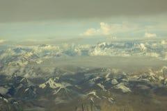 Valle Himalayan de la montaña del desierto con los picos nevosos debajo de un cielo azul con las nubes blancas y grises Silueta d imagen de archivo