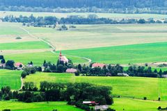 Valle nebbiosa di Broumovsko in repubblica Ceca con i campi ed i prati verdi Vasto panorama del villaggio di Viznov nel Sudetes Fotografia Stock Libera da Diritti