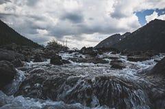 Valle oscuro de la montaña del abatimiento a lo largo del río de la montaña Fotografía de archivo