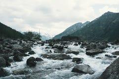 Valle oscuro de la montaña del abatimiento a lo largo del río de la montaña foto de archivo