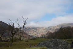 Valle pastoral en primavera con las nubes que obscurecen la montaña iluminada por el sol en distancia fotos de archivo libres de regalías