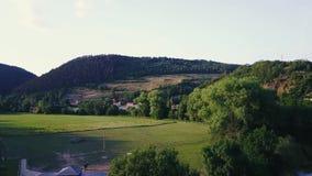 Valle rural entre las colinas, vuelo de la encuesta aérea sobre pequeñas casas con los tejados rojos almacen de video