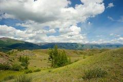 Valle soleado hermoso entre las montañas con las nubes enormes Fotos de archivo libres de regalías