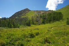 Valle soleado hermoso entre las montañas con las nubes enormes Imagenes de archivo