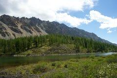 Valle soleado hermoso entre las montañas con las nubes enormes Imagen de archivo libre de regalías