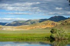 Valle soleado hermoso entre las montañas con las nubes enormes Imagen de archivo