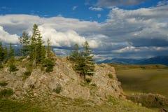 Valle soleado hermoso entre las montañas con las nubes enormes Fotografía de archivo libre de regalías