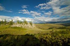 Valle soleado hermoso entre las montañas con las nubes enormes Fotografía de archivo
