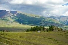 Valle soleado hermoso entre las montañas con las nubes enormes Foto de archivo libre de regalías