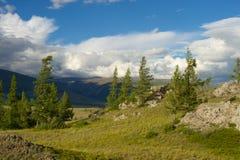 Valle soleado hermoso entre las montañas con las nubes enormes Fotos de archivo