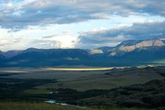 Valle soleado hermoso entre las montañas con las nubes enormes Imágenes de archivo libres de regalías