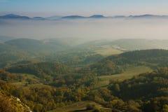 Valle verde con le montagne in nebbia Immagini Stock