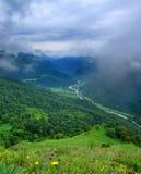 Valle verde con un camino y un río de serpenteo. Foto de archivo libre de regalías