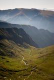 Valle verde con un fiume ed i fianchi di una montagna fotografia stock libera da diritti