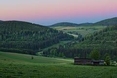 Valle verde fertile con i campi fertili e foresta sotto un cielo rosa di sera al crepuscolo Immagine Stock Libera da Diritti