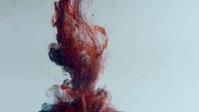 Vallend en langzaam mengt rode en blauwe verf in water,