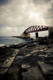 Valletta Bridge along coastline of Malta. Valletta Bridge along rocky coastline of Malta on cloudy day Stock Photos