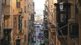 Valletta city downtown side street. Old tall buildings with balconies on narrow side street of Valletta city centre center, capital of Malta stock video footage