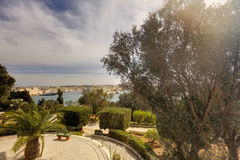 Valletta city harbor area and an outdoor park at Malta, with many historic buildings along the coastline.  Royalty Free Stock Images