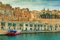 Valletta embankment with traditional colorful doors and anchored ship. Beautiful Valletta embankment with traditional colorful doors and anchored ship, Malta Stock Image