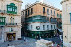 Tourists visiting Valletta city. VALLETTA, MALTA - AUGUST 21, 2017: Tourists walking in Valletta city and enjoying a plenty afternoon in the historical center Royalty Free Stock Image