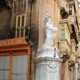 Valletta, Malta, August 2015. View of the Maltese house with a statue of the Apostle Paul and many shops on the lower floor. royalty free stock photography