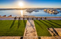 Valletta, Malta - Beautiful sunrise at the famous saluting batte. Ry of Valletta with Grand Harbor and Senglea and Brigu at background. Blue sky and sunlight Stock Image