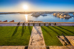 Valletta, Malta - Beautiful sunrise at the famous saluting battery of Valletta. With Grand Harbor and Senglea and Brigu at background. Blue sky and sunlight Royalty Free Stock Images
