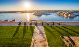 Valletta, Malta - Beautiful sunrise at the famous saluting battery of Valletta with Grand Harbor. And Senglea and Brigu at background. Blue sky and sunlight Royalty Free Stock Image
