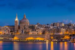 Valletta, Malta - Blue hour at the famous St.Paul`s Cathedral and the city of Valletta. With blue sky Royalty Free Stock Photography