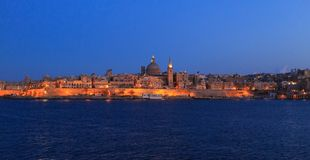 Valletta, Malta in the evening. Panoramic view of illuminated historic island and the dome of Carmelite Church and St Paul`s tower. Valletta, Malta in the Royalty Free Stock Photo