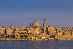 Valletta, Malta - The famous St.Paul`s Cathedral and the ancient. City of Valletta at sunset with clear blue sky Stock Image