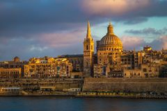 Valletta, Malta - Golden hour at the famous St.Paul`s Cathedral and the city of Valletta. At sunset Royalty Free Stock Image