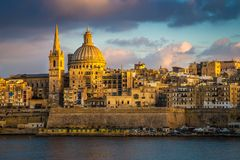 Valletta, Malta - Golden hour at the famous St.Paul`s Cathedral and the city of Valletta. With clouds Stock Photography