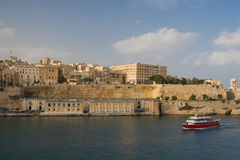 Valletta, Malta Harbor. A photo of Vallette Malta from the harbor. The photo has a red and white ship in the foreground Stock Photos