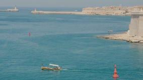 VALLETTA MALTA - JULI 1, 2016: Sikt för fågelöga på folk som nära simmar på traditionell maltese fartygluzzu i den Malta fjärden lager videofilmer