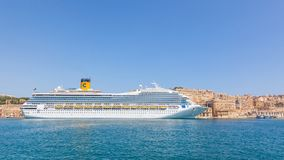 The Costa Magica in Malta. VALLETTA, MALTA - JUNE 29, 2012: The Costa Magica, a cruise ship of the Costa Crociere cruise line, moored alongside traditional Stock Photography