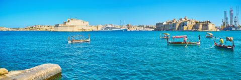 Panorama of Grand Harbour with dghajsa boats, Valletta, Malta. VALLETTA, MALTA - JUNE 17, 2018: The dghajsa and luzzu traditional Maltese boats at Quarry Wharf Royalty Free Stock Photos